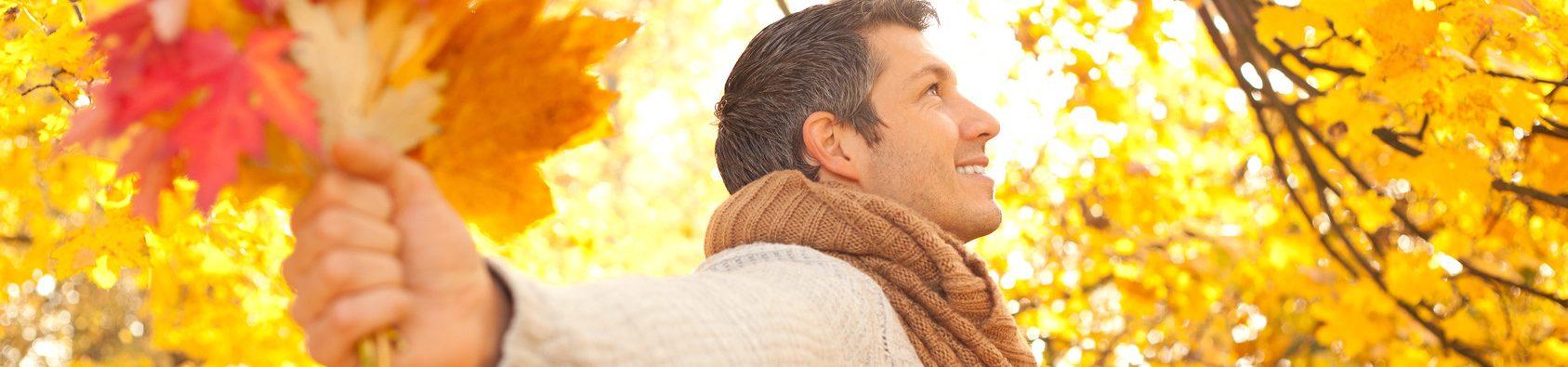 Homme en forêt admirant les couleurs de l'automne